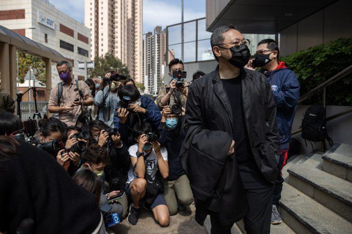 """MORDAZA. El activista y profesor de derecho Benny Tai Yiu-ting (der.) se presenta ante la policía de Hong Kong, luego de ser incluido en la última lista de imputados por """"conspiración de subversión""""."""