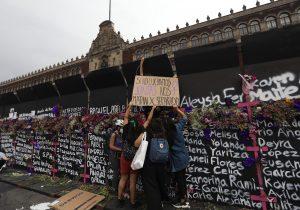 MÉXICO. Mujeres colocan flores y carteles con nombres de víctimas por feminicidios, en cercos metálicos instalados por el Gobierno.