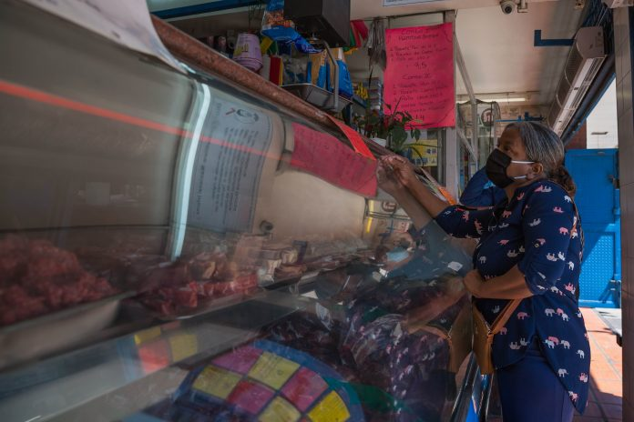 Mercado. Una mujer entrando a una carnicería, el 10 de marzo de 2021, en Caracas. (EFE)