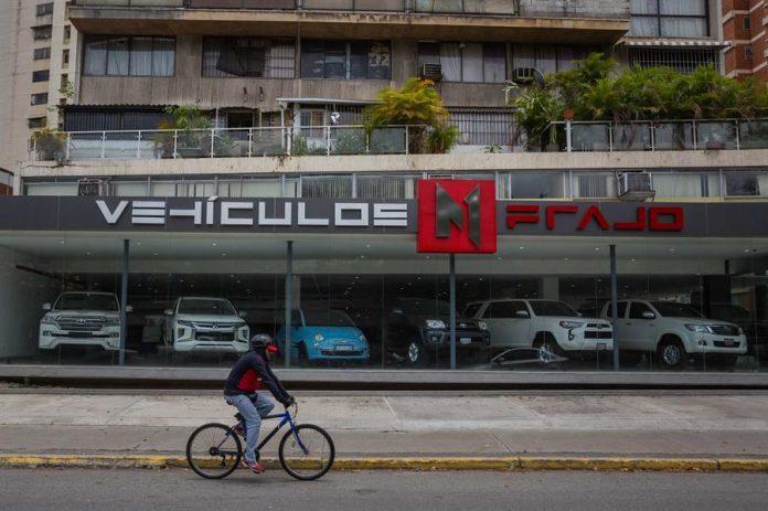 PANORAMA. Un ciclista pasa frente a un negocio de venta de carros usados el 29 de marzo de 2021 en Caracas (Venezuela).