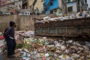 SITUACIÓN. Una mujer busca comida en la basura el 29 de marzo de 2021 en Caracas (Venezuela).