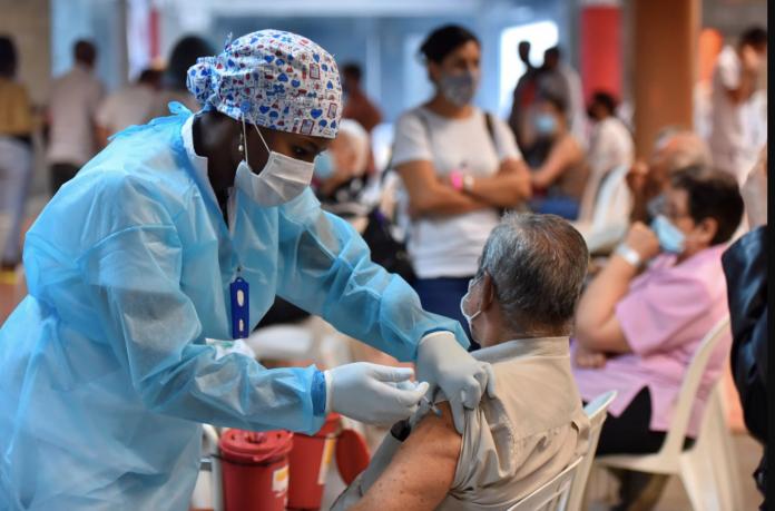 CASO. Una enfermera vacuna a un adulto mayor hoy, en el estadio Pascual Guerrero de Cali (Colombia). EFE/ Ernesto Guzman Jr
