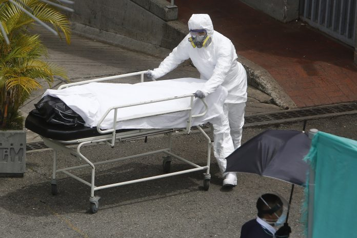 Casos. Personal sanitario transporta el cuerpo de una víctima Covid-19 en el Hospital General de Medellín (Colombia). (EFE)