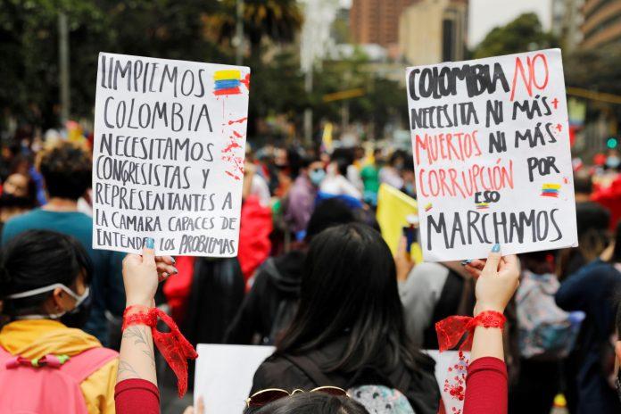 Rechazo. Una mujer sostiene dos carteles durante una protesta contra la violencia ocurrida en las protestas, en el Parque Nacional de Bogotá (Colombia). (EFE)