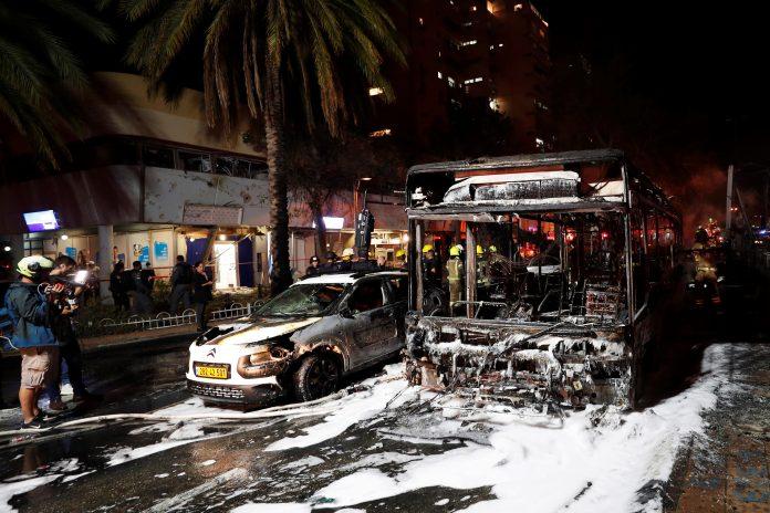 Embestida. Vehículos dañados tras un ataque con cohetes, en la ciudad de Holon, cerca de Tel Aviv, el 11 de mayo de 2021. EFE