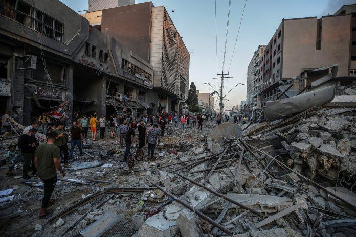 Bombardeos. Palestinos inspeccionan los escombros de la torre Al-Shorouq, destruida después de un ataque israelí en la ciudad de Gaza, el 12 de mayo de 2021. (EFE)